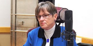 Gov. Laura Kelly prepares for a podcast recording at Kansas Reflector's office. (Sherman Smith/Kansas Reflector)