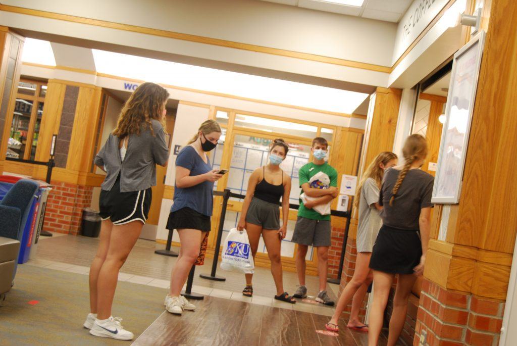 University of Kansas chancellor Doug Girod says two fraternities have been issued cease-and-desist orders to cease noncompliance with county health regulations and university policy designed to inhibit spread of COVID-19. Here students wait for food orders at the Kansas Union ahead of Monday's start of fall semester classes. (Tim Carpenter/Kansas Reflector)