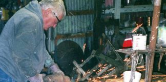 M.T. Liggett, an extraordinary folk artist who created masterpieces out of a farm shop in Mullinville, works on a metal sculpture. The late artist's roadside expressions made of old machinery parts is the basis of a visitor center being developed to display and preserve his work. (Submitted/Kansas Reflector)