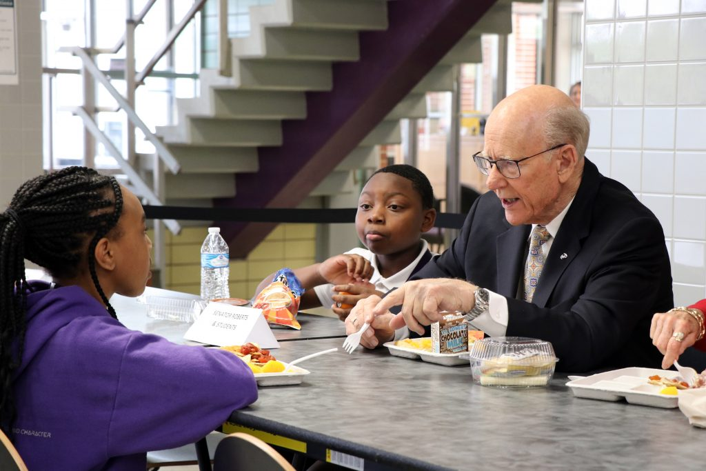 U.S. Sen. Pat Roberts, a Kansas Republican closing out a 40-year career in the U.S. House and Senate, shares lunch with children. He chaired Senate and House agriculture committees, which have jurisdiction over food programs. (Submitted/Kansas Reflector)