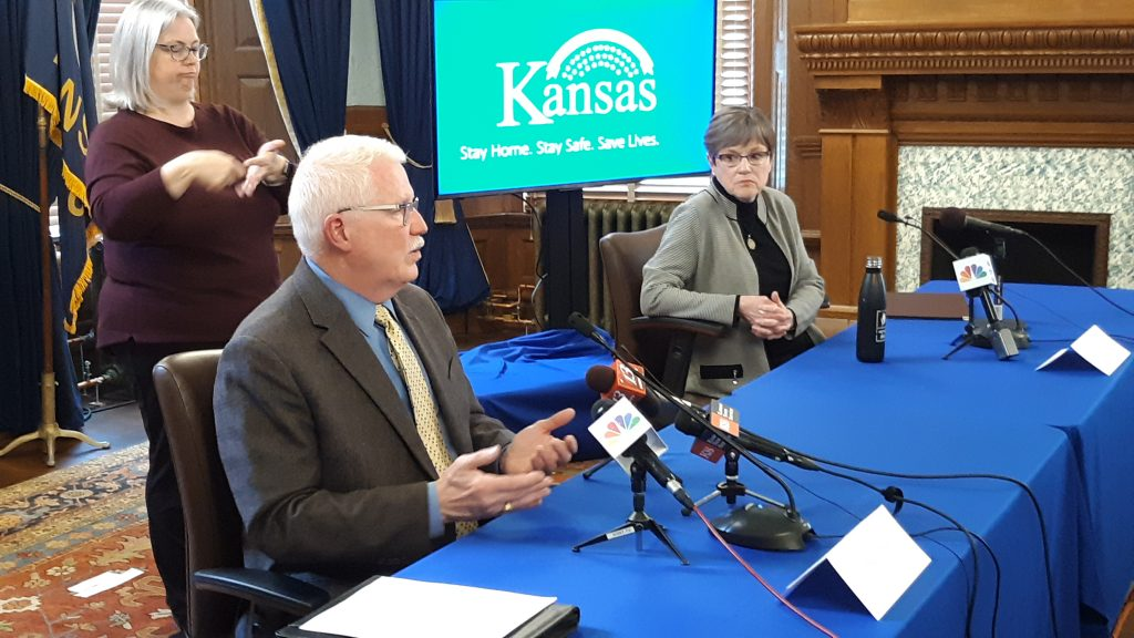 Kansas organizations advocating for people with disabilities and elderly individuals are urging Lee Norman, left, secretary of the Kansas Department of Health and Environment, and Gov. Laura Kelly to resume and expand public disclosure of COVID-19 clusters. (Tim Carpenter/Kansas Reflector)