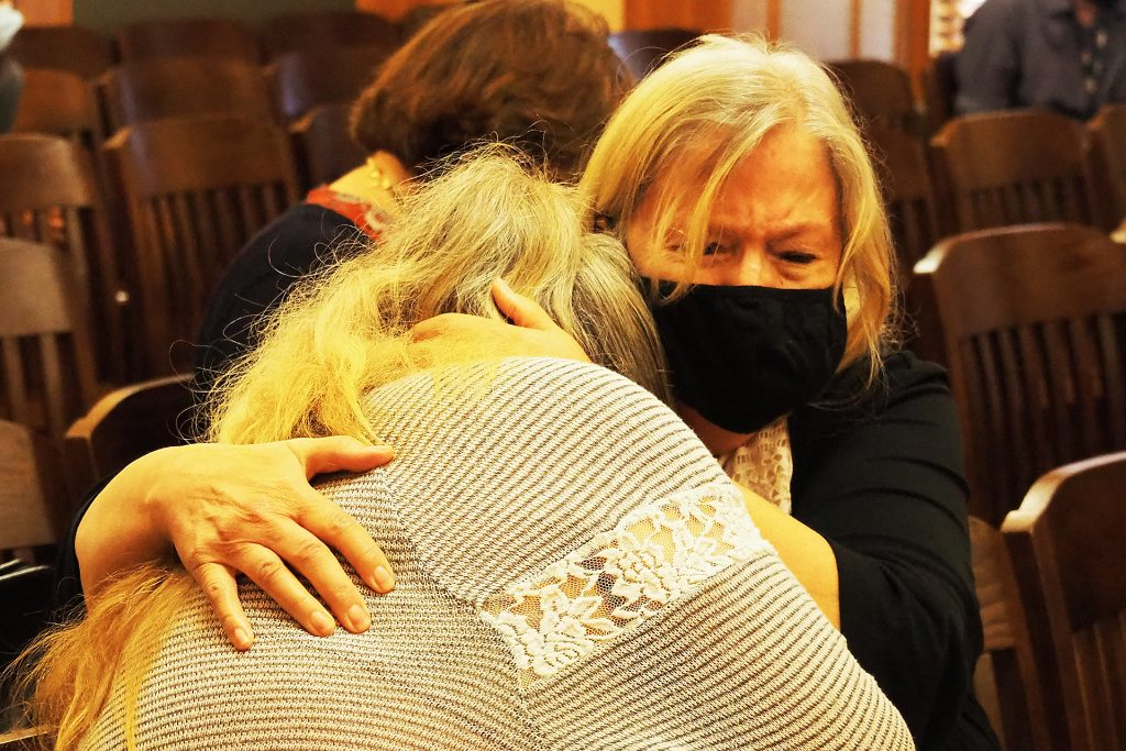 Kathy Winters, facing, hugs Cindy Poe during a hearing on foster care Monday in which they described the personal agony of having their grandchildren placed in foster care by the state of Kansas. (Sherman Smith/Kansas Reflector)