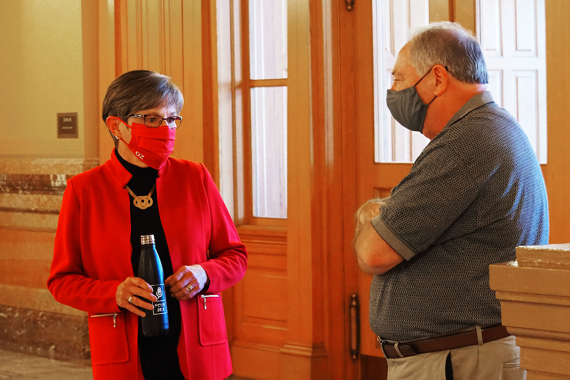 Gov. Laura Kelly, a Topeka Democrat, speaks at the Capitol with Senate Majority Leader Jim Denning, an Overland Park Republican. They disagreed on moving a portion of federal COVID-19 aid into the state's shrinking unemployment trust fund. (Sherman Smith/Kansas Reflector)