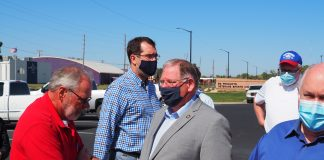 Kansas politicians have different attitudes about wearing masks to prevent spread of COVID-19. At this event in El Dorado, Rep. Will Carpenter, left, chose not to wear a mask, while Attorney General Derek Schmidt, center, Kansas House Majority Leader Dan Hawkins and U.S. Rep. Ron Estes wore a mask. (Tim Carpenter/Kansas Reflector)