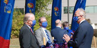U.S. Sen. Jerry Moran, right, and University of Kansas chancellor Doug Girod, center, talk Thursday during a ceremony to celebrate $7.8 million in federal funding for construction of a $24 million campus building to support growth of technology and bioscience companies working collaboratively with KU researchers. (Tim Carpenter/Kansas Reflector)