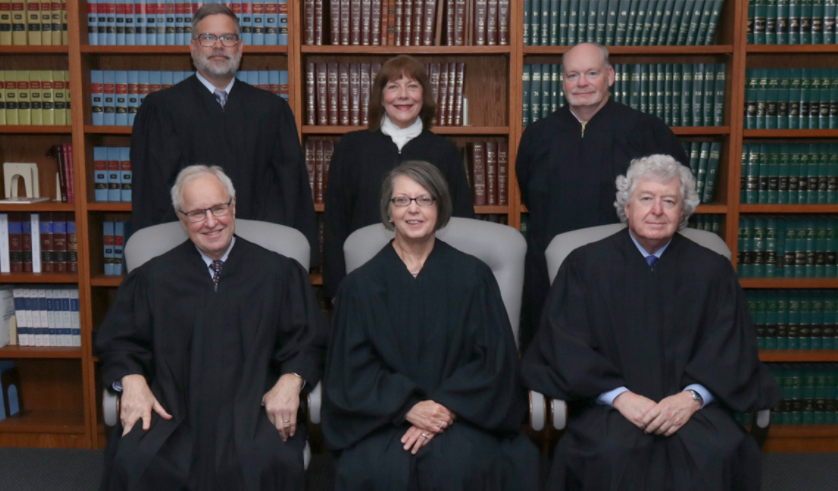 The Kansas Supreme Court unanimously reversed a lower court ruling that found a 2013 state worker compensation law to be unconstitutional. Members of the court, seated from left: Justice Eric Rosen; Chief Justice Marla Luckert; Justice Dan Biles. Standing from left: Justice Caleb Stegall; Justice Evelyn Wilson; Justice K.J. Wall. Not pictured: Melissa Taylor Standridge, who was recently appointed to the court. (Kansas Supreme Court/Kansas Reflector)