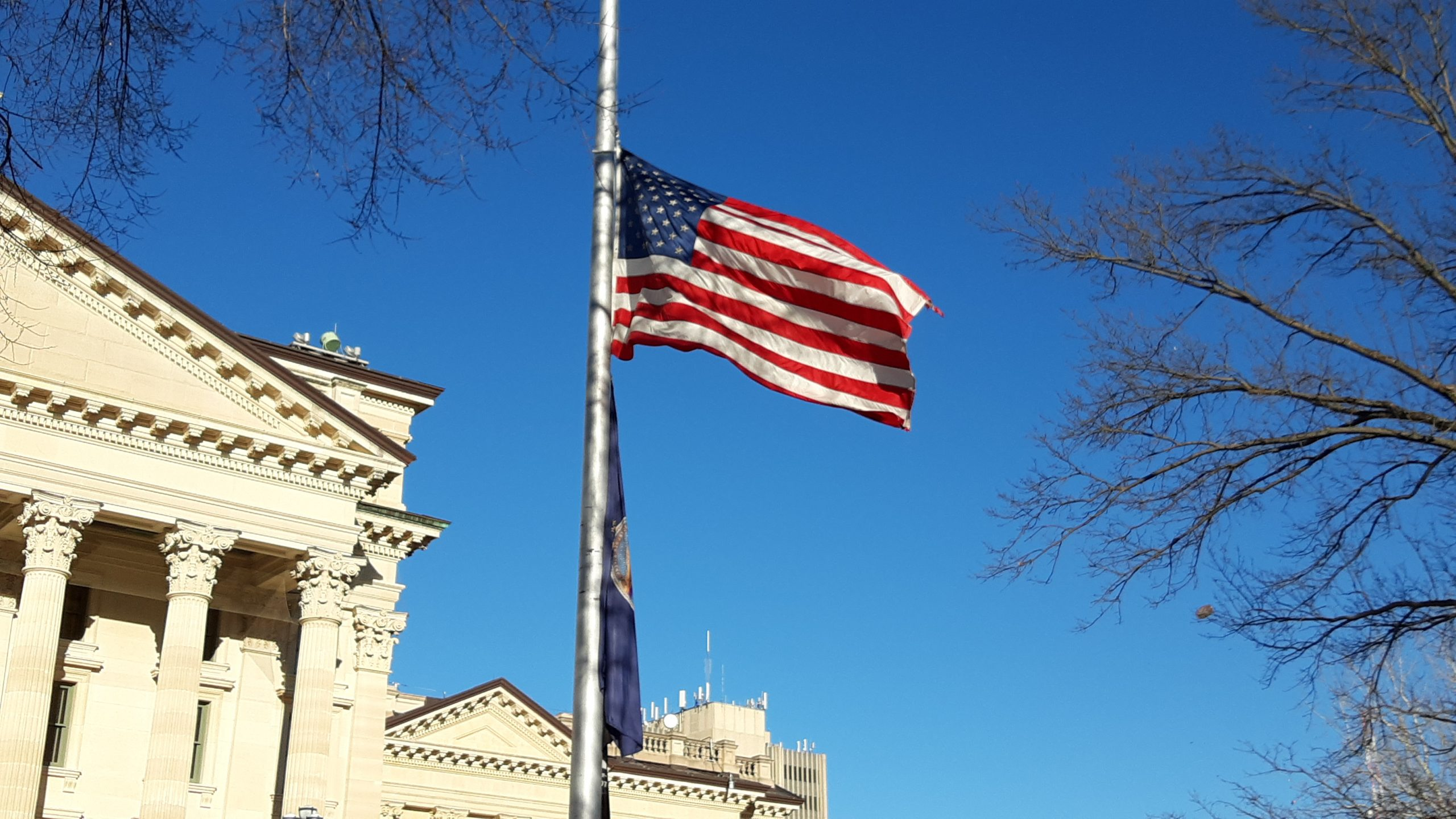 Gov. Laura Kelly instructed flags in Kansas fly at half-staff through Monday in honor of more than 2,000 Kansans who died after infected with COVID-19. (Tim Carpenter/Kansas Reflector)