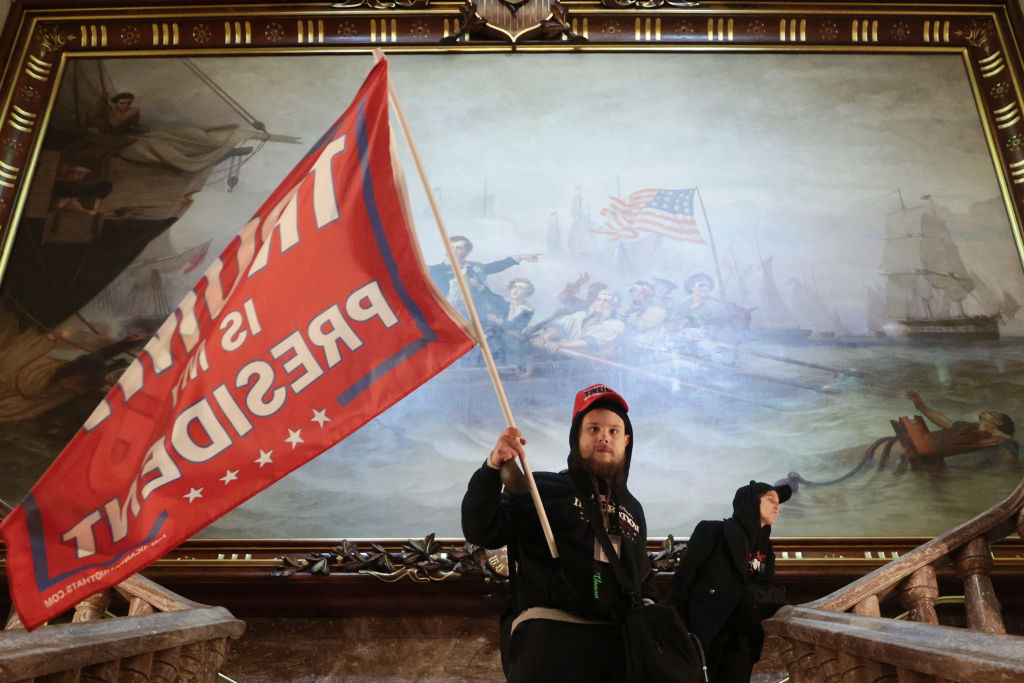 A protester holds a flag in support of President Donald Trump inside the U.S. Capitol building near the Senate chamber in Washington, D.C. Congress held a joint session Wednesday to ratify President-elect Joe Biden's 306-232 Electoral College win over Trump. A group of GOP senators said they would reject the Electoral College votes of several states unless Congress appointed a commission to audit the election results. (Win McNamee/Getty Images)