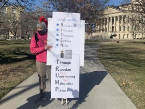 Topeka resident Graham Bonsall takes a stand at the Kansas Capitol on Wednesday in support of the election of President Joe Biden in a contest challenged by supporers of former President Donald Trump. (Noah Taborda/Kansas Reflector)