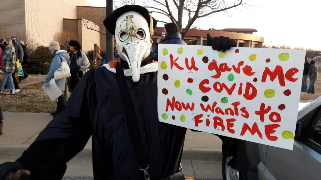 Gregory Cushman, an associate professor of environmental history at the University of Kansas, marched with faculty and students on Tuesday night to raise awareness about potential damage of administration plans to downsize the staff and eliminate degree programs to address budget problems. (Tim Carpenter/Kansas Reflector)