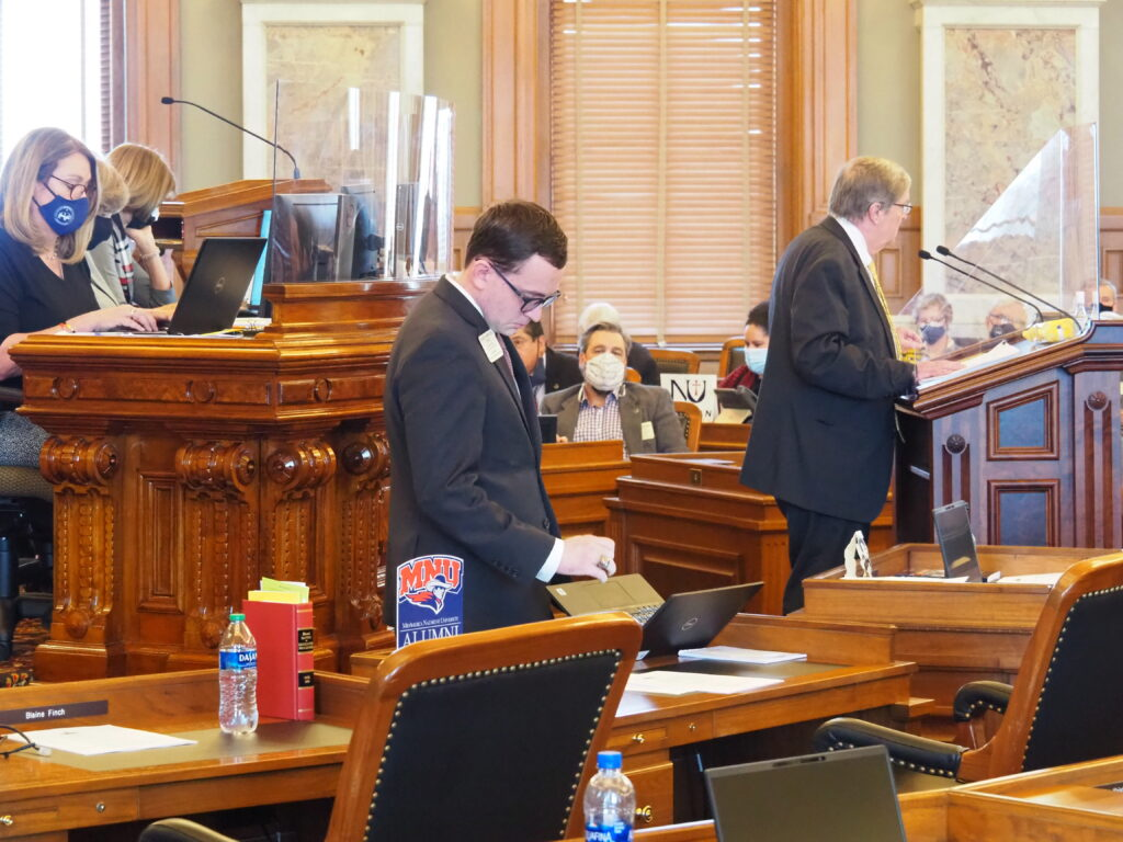 Frustrated Republican Rep. Blake Carpenter, center, idles in the Kansas House chamber while Democratic Rep. Vic Miller makes good on a promise to engage in a presentation on a federal voting rights bill. Carpenter and GOP allies shut Miller down with an obscure rule that found Miller guilty of being tedious. (Tim Carpenter/Kansas Reflector)
