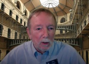 Mark Desetti, a representative of the Kansas National Education Association, testified against a bill requiring a new civics testing mandate for high school students. He testified remotely with a prison scene as a background. (Screen capture/Kansas Reflector)