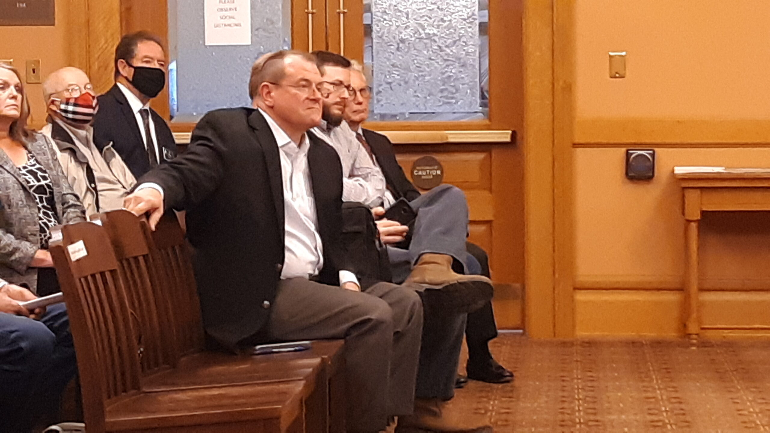 Anderson County resident Mike Burns, center, registered support Monday for a Senate bill that would impose sweeping regulations on wind farm developments and protect property rights of people living in rural areas with terrain and breezes to support turbines. (Tim Carpenter/Kansas Reflector)