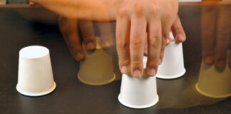 Motion blurred image of male hands playing shell game
