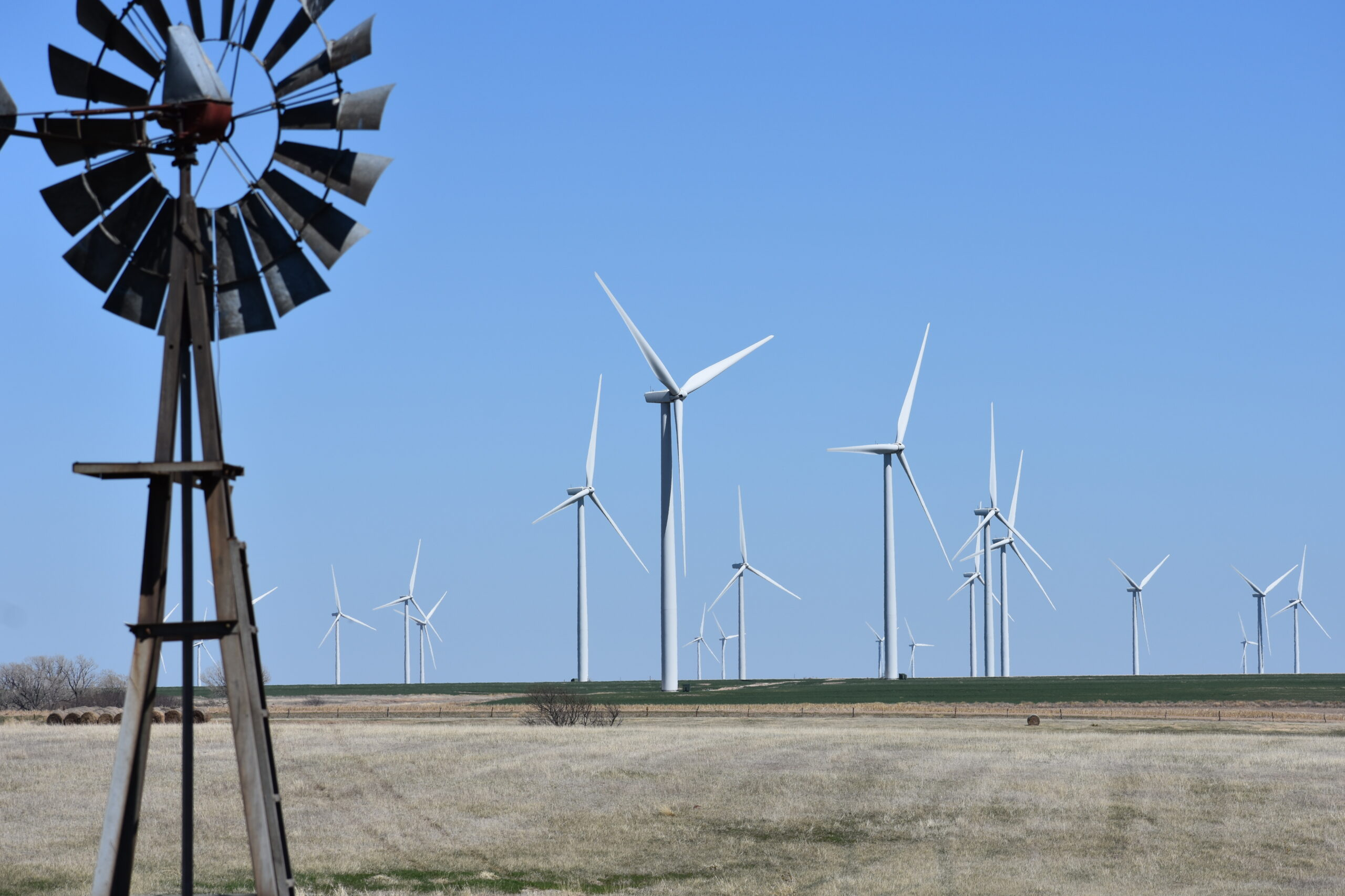 An old farm windmill used to pull water from the ground stands among dozens of modern wind turbines constructed in southwest Kansas as the state worked to harness the breeze to produce electricity. (Jill Hummels for the Kansas Reflector)