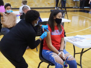 A participant looks away at the moment a COVID-19 vaccination needle makes contact Monday during a temporary clinic at Topeka High School. (Tim Carpenter/Kansas Reflector0