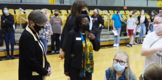 Gov. Laura Kelly and Topeka school district superintendent Tiffany Anderson chat Monday with Laura Vandruff, 15, as she receives a COVID-19 vaccination at Topeka High School. (Tim Carpenter/Kansas Reflector)