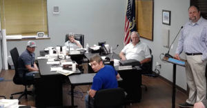 Justin Meeks, standing right, advised the Bourbon County Commission that Jacqie Spradling's time as county prosecutor would come to a end without commission action. On Wednesday, Spradling quit her job. (Screen capture/Kansas Reflector)