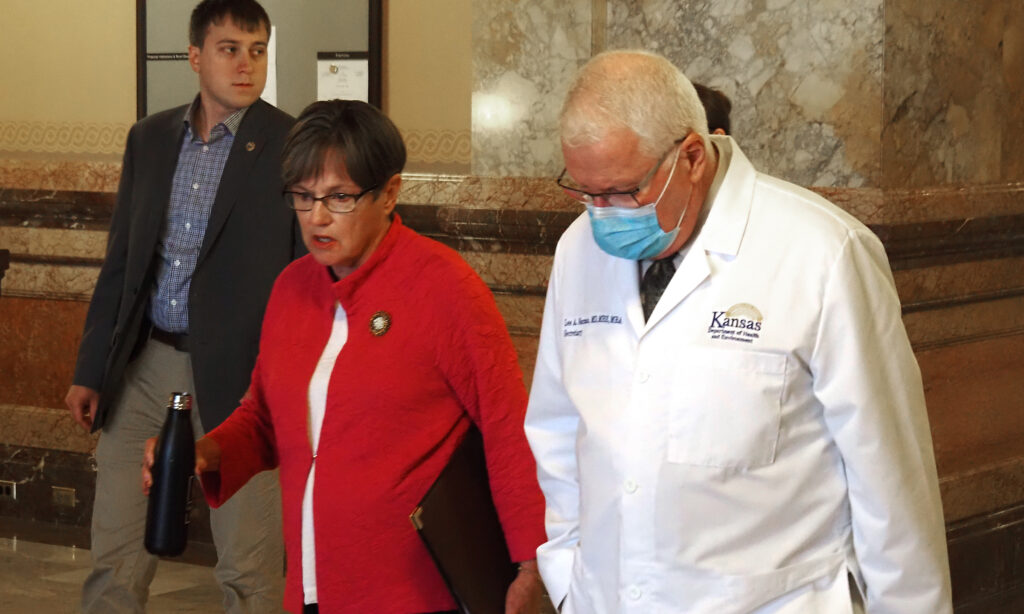Gov. Laura Kelly walks through the Capitol to a news conference Wednesday with Lee Norman, secretary of the Kansas Department of Health and Environment, to discuss the need for people to wear masks against the COVID-19 variant. (Tim Carpenter/Kansas Reflector)